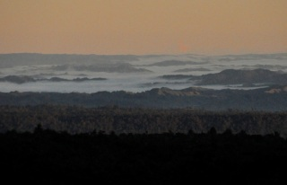In the distance, viewing from Chateau Tongariro in the evening, mountaintops protruding above a layer of clouds