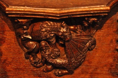 Detail of the misericord carving, a lion fighting a dragon